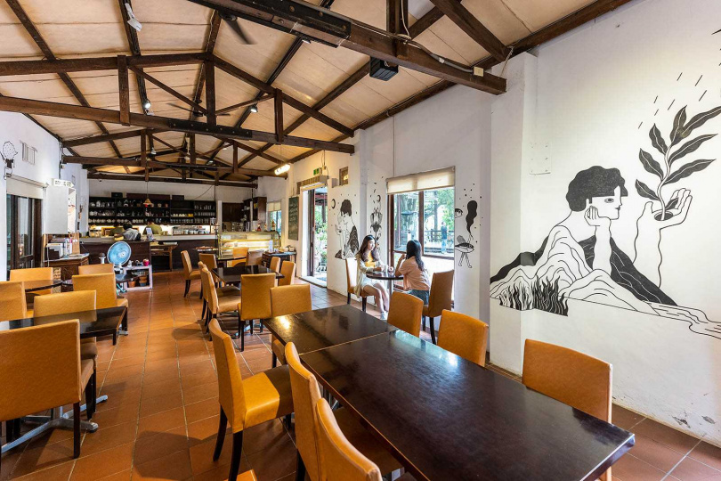 「沙湖壢咖啡館」是由70多年的磚造平房所改建,牆壁上的畫作很吸睛。(圖/焦正德攝)