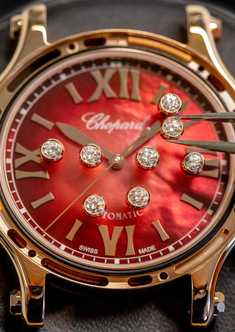 Chopard「Happy Sport」系列腕錶,紅色珍珠母貝錶盤款,錶盤中央鑲有8顆總重0.4克拉的滑動鑽石。(圖╱Chopard提供)