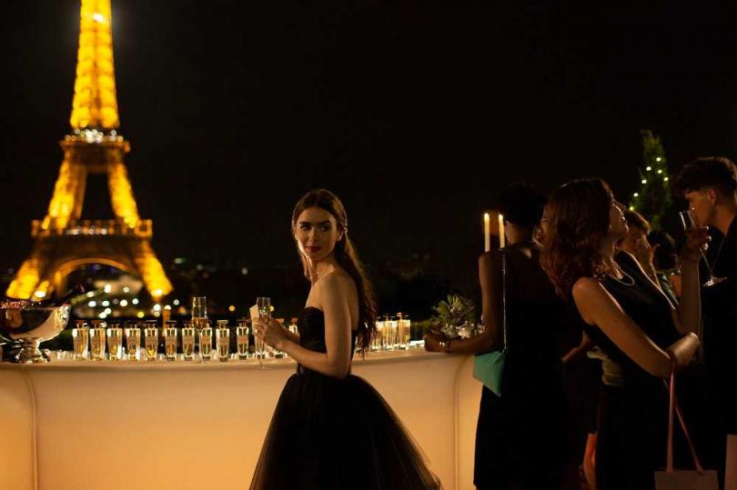 莉莉柯林斯在《艾蜜莉在巴黎》中,於巴黎鐵塔地標前,身著經典黑色小禮服亮麗登場。(圖/Netflix提供)