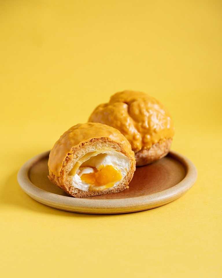 「PABLO杏桃蕾雅泡芙」。將雞蛋、牛奶、奶油乳酪、鮮奶油等加入熬煮成蕾雅起司卡士達,再加入鮮奶油提升滑順感後,與特製的杏桃水蜜桃醬分層豪邁擠入泡芙中成為內餡。(45元)