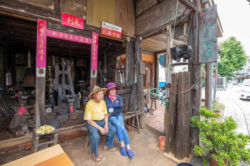 「泉利鐵舖」的老匠人李一男訴說老店歷史,也常吸引遊客前來造訪合影。(圖/宋岱融攝)